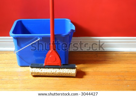 mop and blue bucket on hardwood floors with red wall in background - stock photo
