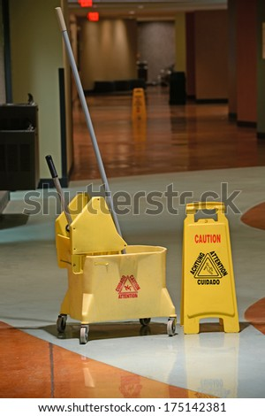 Mop and Bucket with caution sign on wet floor - stock photo