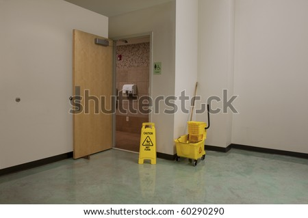Mop bucket and caution sign outside the open door of a Women's Restroom that is being cleaned - stock photo