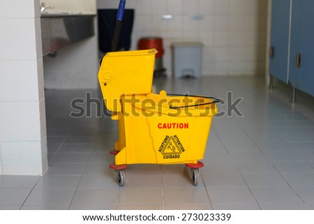 Mop bucket on wet floor in toilet. - stock photo