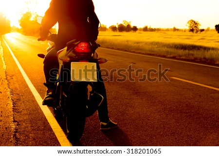 moped drivers on the road with sunset - stock photo