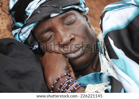 MOPTI, MALI, AFRICA - AUGUST, 26, 2011 African woman sleeping after a day of work in the market of Mopti - stock photo