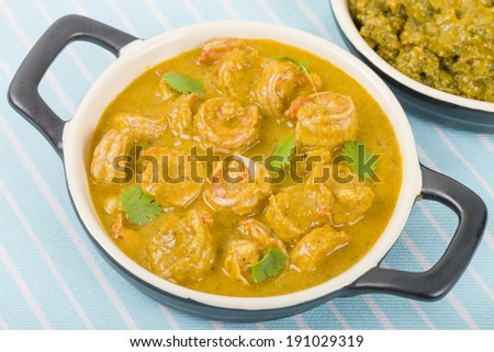 Moqueca de Camarao - Brazilian prawns in coconut milk and dende oil. Caruru on background. Food from Bahia. - stock photo