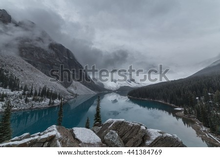 Moraine lake on a foggy morning after a layer of snow fall overnight