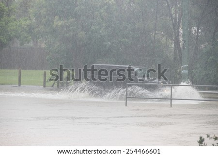 MORAYFIELD, AUSTRALIA - FEBRUARY 21: Cars driving accross flooded roadway caused by Cyclone Marcia on Feburay 21, 2015 in Morayfield, Australia - stock photo