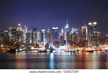 Mordern city night scene. New York City Times Square Manhattan Skyline at night panorama over Hudson River with reflection. - stock photo