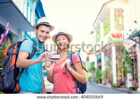 More opportunities for travel. Young traveling couple holding credit card while standing on the asian street holding backpacks. - stock photo