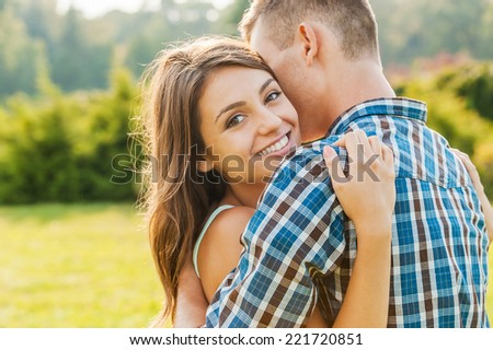 More than love. Beautiful young woman bonding to her boyfriend and smiling at camera while both standing outdoors  - stock photo