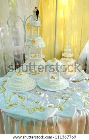 More wedding cake on decorated table - stock photo
