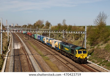 MORETON, UK - APRIL 20: A Freightliner operated freight train passes through a cutting on route to Southampton on April 20, 2016 in Moreton. Freightliner operate a fleet of 80 locos & 1400 wagons