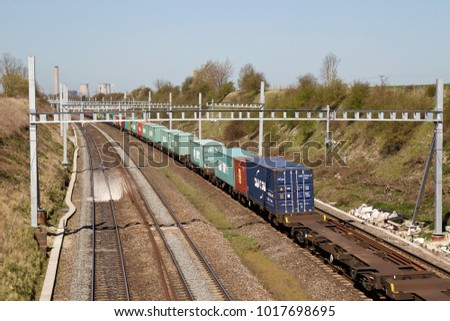 MORETON, UK - APRIL 20: An intermodal diesel freight train heads towards Bristol on April 20, 2016 in Moreton. This service is passing under the yet to be completed electrification program from London
