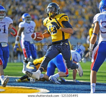 MORGANTOWN, WV - DECEMBER 1: WVU running back Andrew Buie (13) high steps into the end zone for a touchdown during the Big 12 football game December 1, 2012 in Morgantown, WV. - stock photo