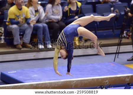 MORGANTOWN, WV - MARCH 8:  A WVU gymnast performs on the balance beam during a dual meet March 8, 2015 in Morgantown, WV.  - stock photo