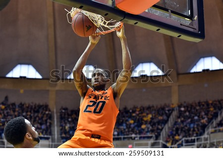 MORGANTOWN, WV - MARCH 7: Oklahoma State Cowboys forward/center Michael Cobbins (20) finishes a slam dunk during the Big 12 Conference college basketball game March 7, 2015 in Morgantown, WV.  - stock photo