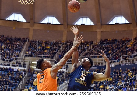 MORGANTOWN, WV - MARCH 7: West Virginia Mountaineers forward Devin Williams (5) shoots over a Cowboy defender during the Big 12 Conference college basketball game March 7, 2015 in Morgantown, WV.  - stock photo