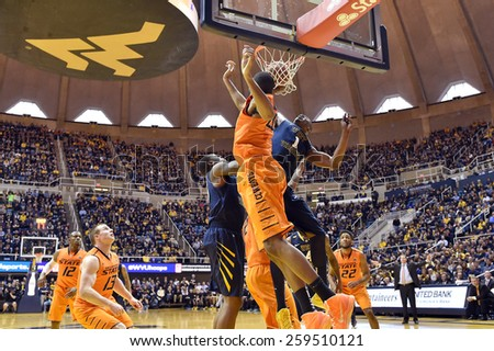 MORGANTOWN, WV - MARCH 7: WVU forward Jonathan Holton (1) scores on an offensive rebound defends during the Big 12 Conference college basketball game March 7, 2015 in Morgantown, WV.  - stock photo