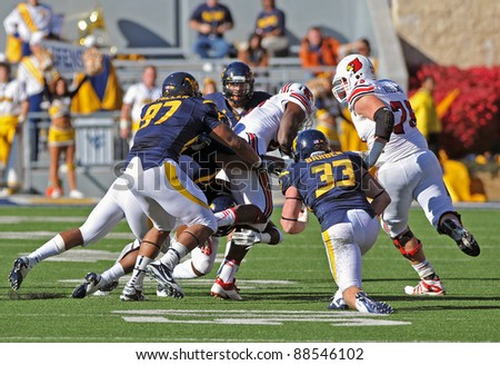 MORGANTOWN, WV - NOVEMBER 5: Louisville receiver Dominique Brown (center, white uniform) is tackled by defenders during the football game against WVU November 5, 2011 in Morgantown, WV.