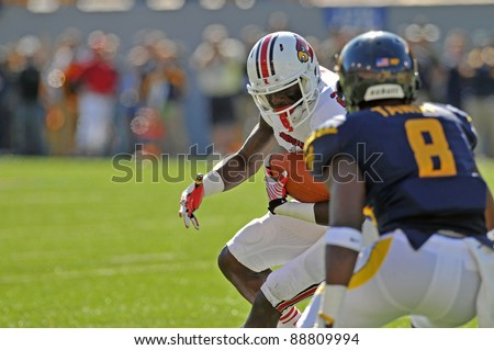 MORGANTOWN, WV - NOVEMBER 5: Louisville receiver Michaelee Harris (white) prepares to be hit after making a catch in the Big East football game against WVU November 5, 2011 in Morgantown, WV - stock photo