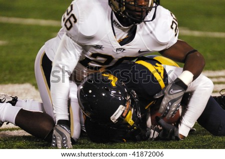 MORGANTOWN, WV - NOVEMBER 27: Unnamed WVU player down on the turf following a tackle in the game November 27, 2009 in Morgantown, WV. - stock photo