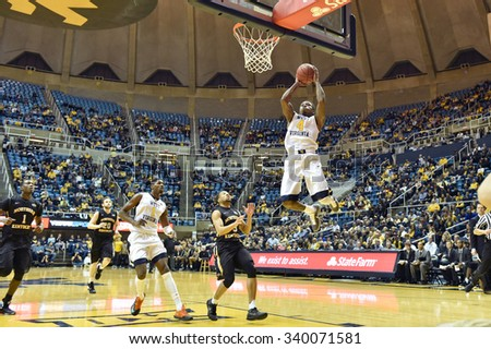 MORGANTOWN, WV - NOVEMBER 13: West Virginia Mountaineers guard Daxter Miles Jr. (4) drives to the basket for a shot during the basketball game November 13, 2015 in Morgantown, WV.  - stock photo