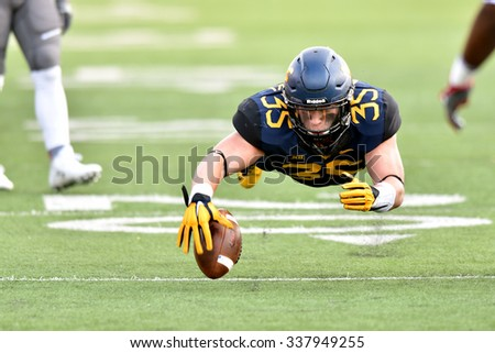 MORGANTOWN, WV - NOVEMBER 7: West Virginia Mountaineers linebacker Nick Kwiatkoski (35) leaps to cover a loose ball during the football game November 7, 2015 in Morgantown, WV. - stock photo