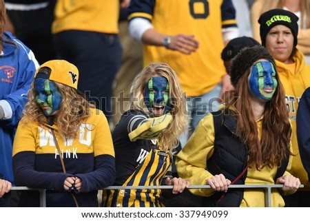 MORGANTOWN, WV - NOVEMBER 7: WVU fans in the student section, complete with face paint, cheer during the football game November 7, 2015 in Morgantown, WV. - stock photo