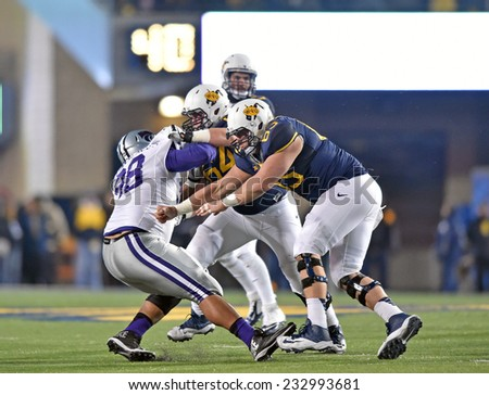 MORGANTOWN, WV - NOVEMBER 20: WVU offensive linemen Mark Glowinski (64) and Tyler Orlosky (65) team up to block a K-State defender during the Big 12 football game November 20, 2014 in Morgantown, WV.  - stock photo