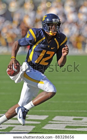 MORGANTOWN, WV - NOVEMBER 5: WVU quarterback Geno Smith runs with the ball to escape pressure in a football game against WVU November 5, 2011 in Morgantown, WV. - stock photo