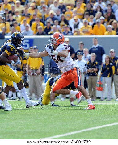 MORGANTOWN, WV - OCTOBER 23: Syracuse University linebacker Mikhail Marinovich (#54) tries to make a tackle against a WVU ball carrier in a Big East game October 23, 2010 in Morgantown, WV. - stock photo