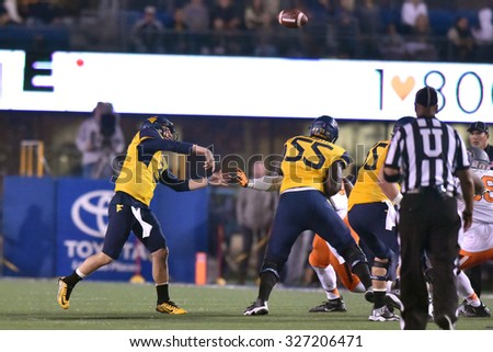 MORGANTOWN, WV - OCTOBER 10:  West Virginia Mountaineers quarterback Skyler Howard (3) throws a pass from the pocket during the Big 12 football game October 10, 2015 in Morgantown, WV.  - stock photo