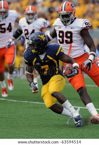 MORGANTOWN, WV - OCTOBER 23: West Virginia University running back Noel Devine (#7) cuts back on a rush with Syracuse defenders chasing October 23, 2010 in Morgantown, WV. - stock photo