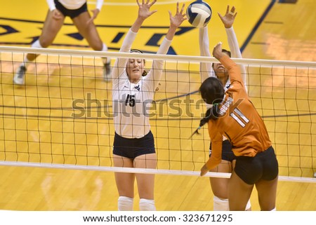 MORGANTOWN, WV - SEPTEMBER 25: West Virginia  hitters Dzeni Hadzisehovic (16) and Bridgette Talia (5)  try to block a Longhorn spike during a volleyball match  September 25, 2015 in Morgantown, WV.  - stock photo