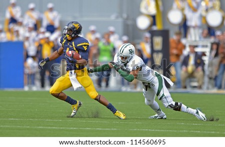 MORGANTOWN, WV - SEPTEMBER 29: West Virginia Mountaineers wide receiver Tavon Austin (l) avoids an open field tackle during a Big 12 conference football game September 29, 2012 in Morgantown, WV. - stock photo