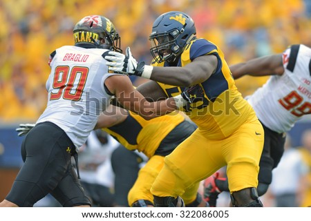 MORGANTOWN, WV - SEPTEMBER 26: WVU offensive lineman Yodny Cajuste(55) blocks in pass protection during the NCAA football game September 26, 2015 in Morgantown, WV.  - stock photo