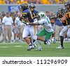 MORGANTOWN, WV - SEPTEMBER 1: WVU running back Shawne Alston (l) carries a Marshall defender on a rush during the first football game of the season September 1, 2012 in Morgantown, WV. - stock photo