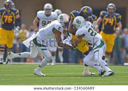 MORGANTOWN, WV - SEPTEMBER 29: WVU wide receiver J.D. Woods (center) is hit hard by two Baylor defenders during a Big 12 conference football game September 29, 2012 in Morgantown, WV. - stock photo