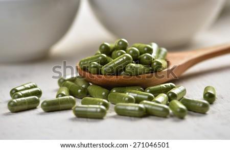 Moringa capsule pills in the woodspoon - stock photo