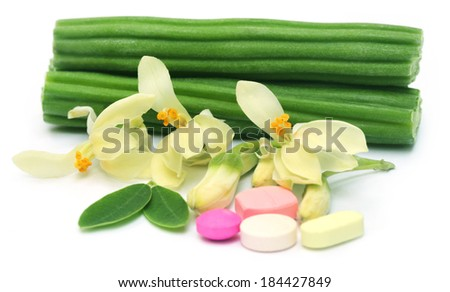 Moringa pills with flower and leaves over white background - stock photo