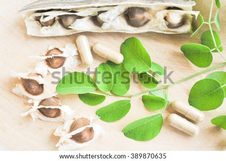 Moringa seeds with leaves,drumstick and powder in capsule in natural light on wood background, selected focus area. Alternative Medicine - stock photo