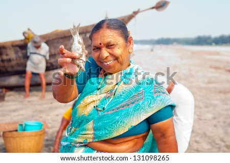 MORJIM, GOA, INDIA - MARCH 11: Indian woman show for sale fresh caught fish on a beach near fisher boat, Morjim, March 11, 2013 in Goa India. This activity will provide a income stream for people.