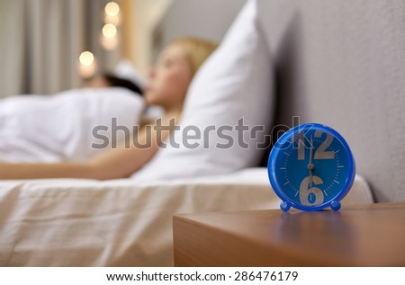 morning, and people concept - close up of alarm clock in bedroom - stock photo