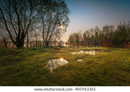 Morning april landscape with puddles on foreground and lake coast on background. - stock photo