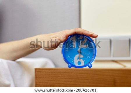 morning, awakening and people concept - close up of female hand on alarm clock in bedroom - stock photo