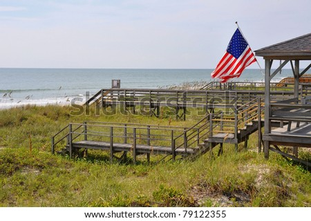 Morning beach scene with American Flag - stock photo