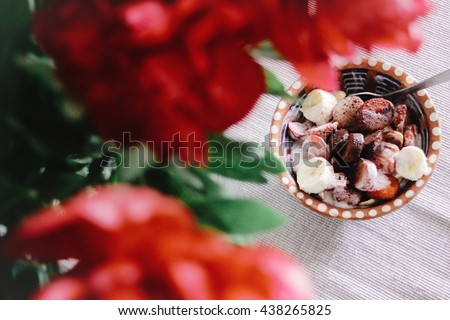 morning breakfast bananas yogurt cereals in bowl, top view at red peonies on old rustic table - stock photo