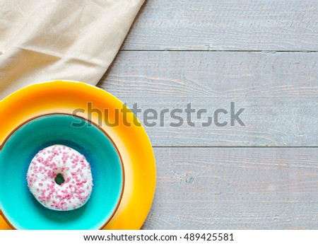 Morning breakfast with colorful Donuts on a rustic wooden background. Top view