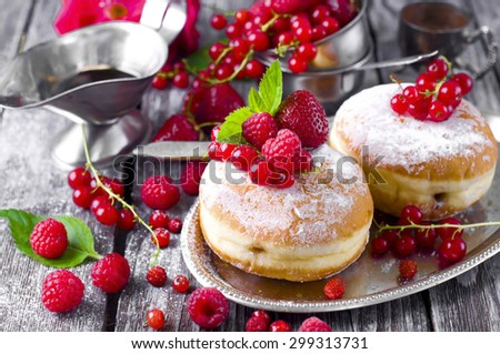 Morning breakfast with mini donuts and berries on plate under powdered sugar on background.   - stock photo