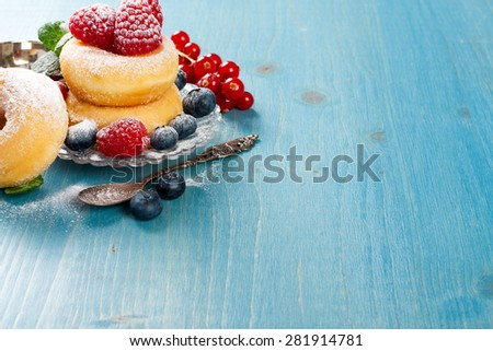Morning breakfast with mini donuts and berries on plate under powdered sugar on blue wooden background.  Tasty donuts closeup. Doughnut. Copy space. - stock photo