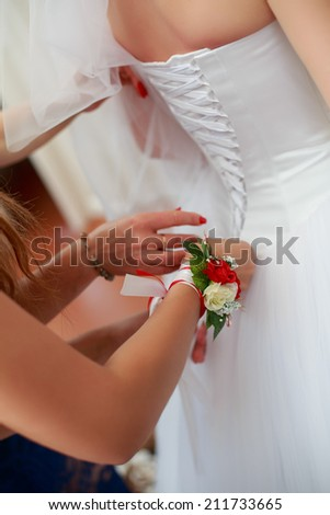 Morning bride. Bridesmaid helping the bride lacing up her dress closeup portrait of a maid of honor helping the bride with her dress - stock photo