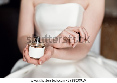 morning bride in a white wedding dress enjoys perfume on wrists